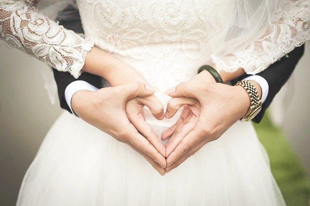 Mariés faisant un coeur avec les mains